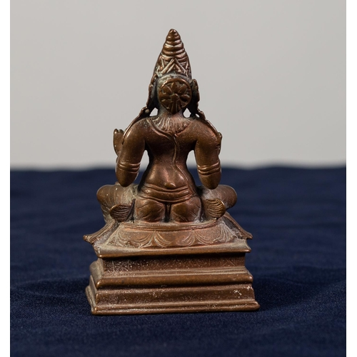 97 - FAR EASTERN BRONZE MODEL OF KALI seated in a traditional pose, on high oblong base, 3 1/2in (8.8cm) ...