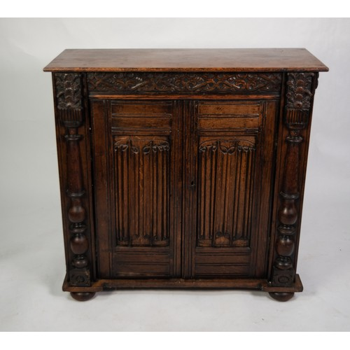 108 - AGED OAK SIDE CABINET, the plain top above a cupboard enclosed with a pair of carved linen-old panel...