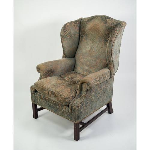 186 - 20th CENTURY GEORGE III STYLE WINGED BACK UPHOLSTERED ARMCHAIR with loose cushion seat, covered in p...