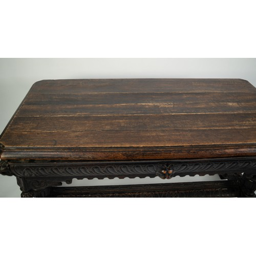 184 - LATE 19th CENTURY FLEMISH CARVED AND DARK STAINED OAK WRITING TABLE, the moulded edge canted top for...