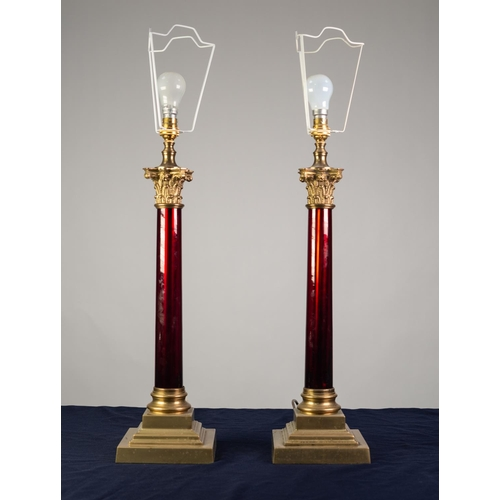 77 - LARGE PAIR OF BRASS AND RED GLASS TABLE LAMPS, each of Corinthian column form with square, stepped b...