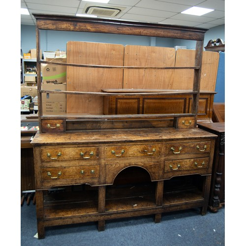 111 - GEORGE III MONTGOMERYSHIRE OAK DRESSER, the open three shelf plate rack with two short drawers to th...