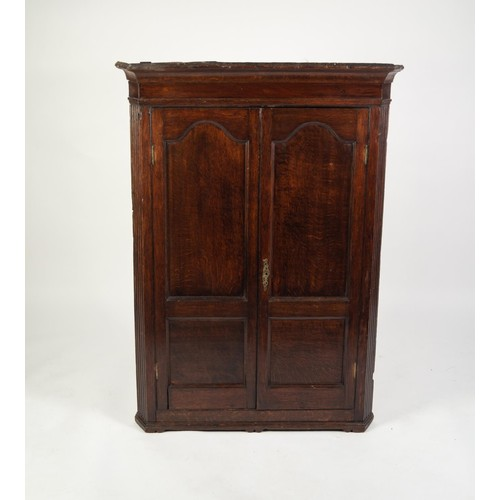 123 - GEORGE III OAK FLAT FRONTED CORNER CUPBOARD, the moulded cornice above a pair of twin panelled cupbo...