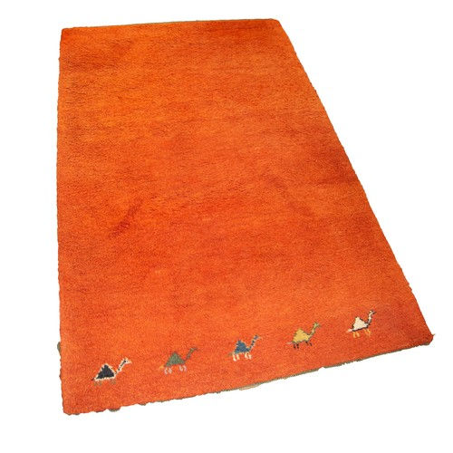 13 - EASTERN MACHINE WOVEN PLAIN ORANGE SMALL CARPET with row of five camels to the bottom edge, 6ft x 4f...
