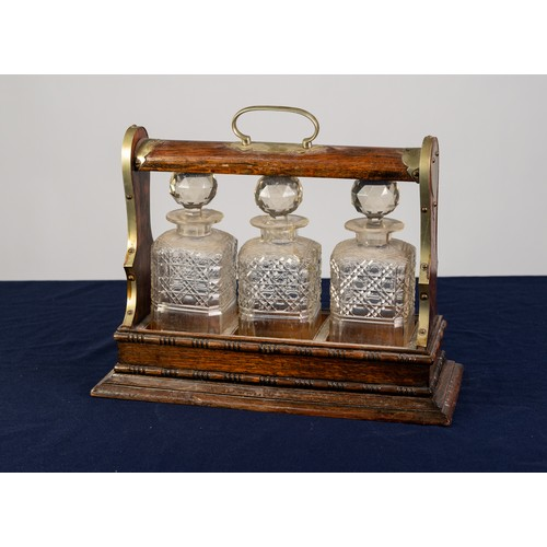 49 - AN EARLY TWENTIETH CENTURY OAK TANTALUS with rubbed EPNS mounts, fitted with three square cut glass ...