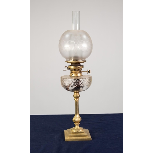 74 - BRASS OIL TABLE LAMP, of slender, panelled baluster form with square, stepped base, cut glass reserv...