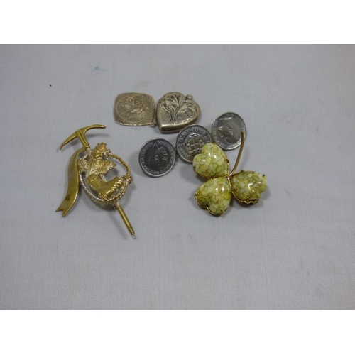 59 - Three brooches to include coin bar, silver locket and St Christopher...