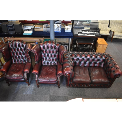 298 - Chesterfield Style Sofa Upholstered in Burgundy Leather with matching Pair of Wingback armchairs