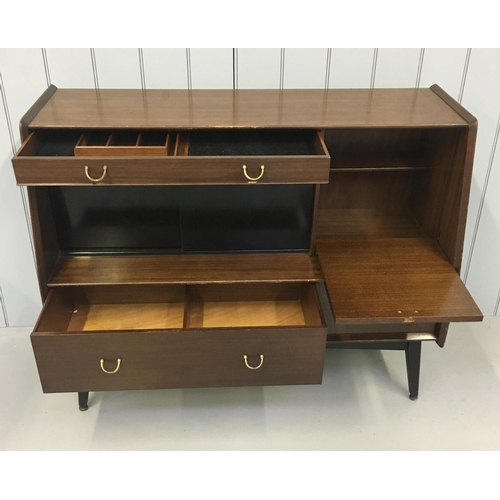 70 - A dark wood mid-century G-Plan Sideboard by Edward Gomme. A divided cutlery drawer sits over a black...