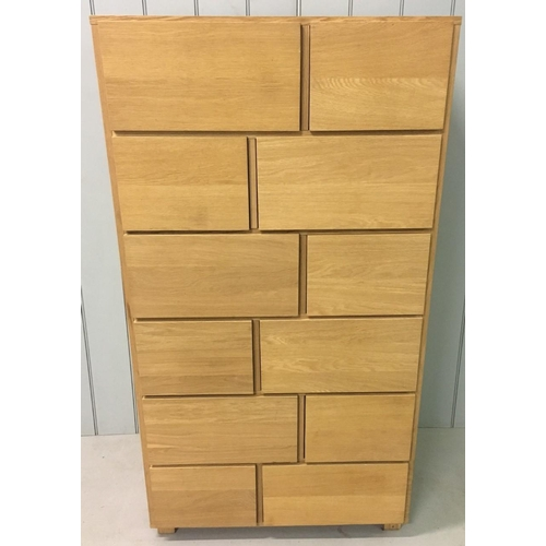 24 - A contemporary, quality tall chest of drawers. Consists of 12 solid Beech, deep drawers supported by...