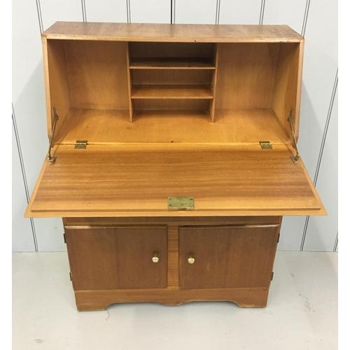 57 - A light-wood bureau. Drop-down desk area above double drawers, in turn over a double cupboard. Dimen...