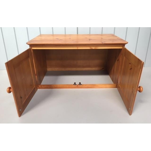 17 - A small pine unit made to sit upon another piece of furniture. 2-door with a hollow base. Dimensions...