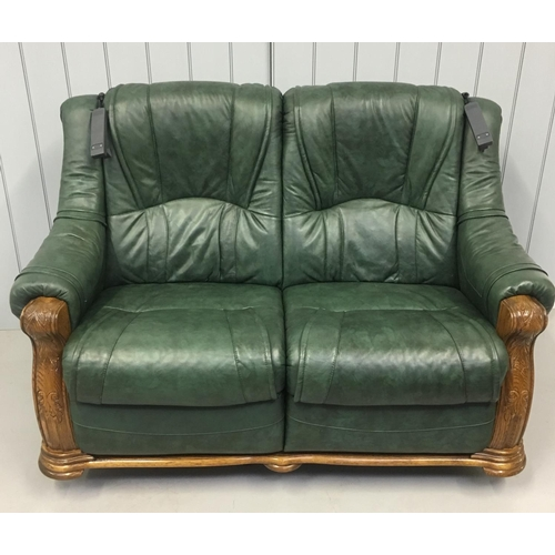 20 - A quality green leather suite, with oak surround. A two seater sofa and two armchairs. Each is a rec...