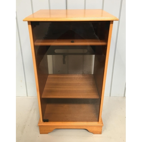 29 - A traditional mid-century teak Hi-Fi cabinet on castors. Smoked glass door with a top shelf for a tu...