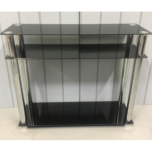 47 - A modern console table, with black-glass shelves, supported by chrome coloured legs. Dimensions(cm) ...