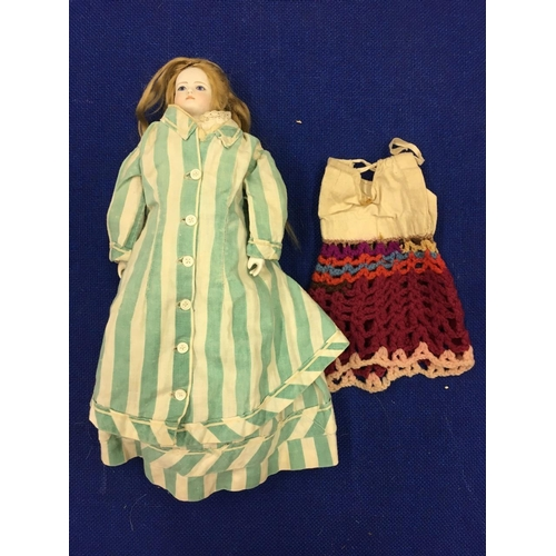 77 - An antique porcelain doll, in hand-made clothing. 27cm tall....