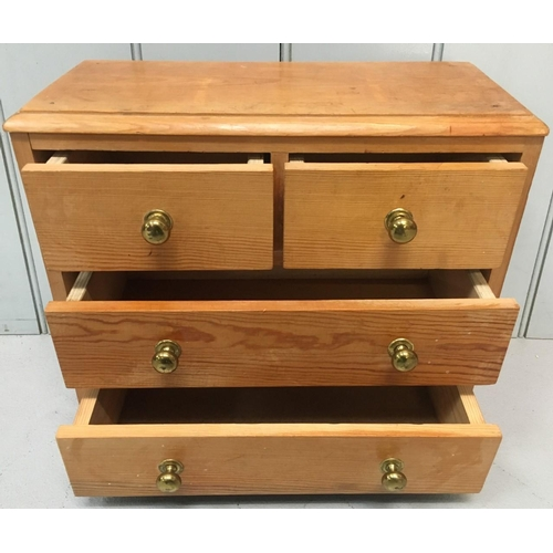 595 - A solid pine, miniature chest of drawers. 2 over 2 drawers. Dimensions(cm) H34 W39 D19...