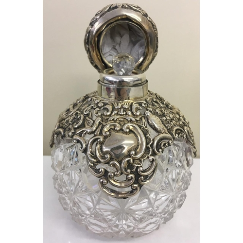 371 - A stunning Silver-collared Scent Bottle. Hallmarked. Chester 1902. Height 13cm.