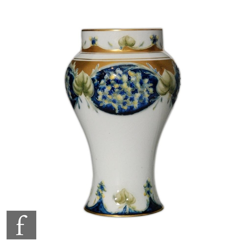 4 - An early 20th Century William Moorcroft Lilac pattern baluster vase decorated with panels of flowers...