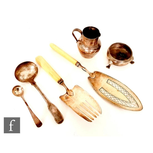 21 - Six items of hallmarked silver to include a Georgian fish slice, a small jug, three other items of f...