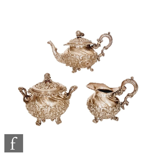26 - A 19th Century continental silver three piece tea set of part wrythen form with embossed foliate scr...