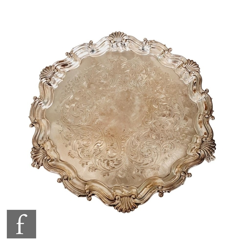 51 - A hallmarked silver circular salver with engraved foliate scroll decoration within scalloped and she...