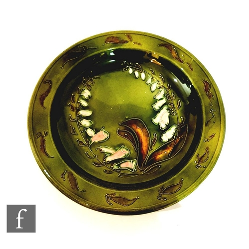 42 - A late 19th Century shallow bowl decorated with tubelined foxgloves and foliage against a green mott...