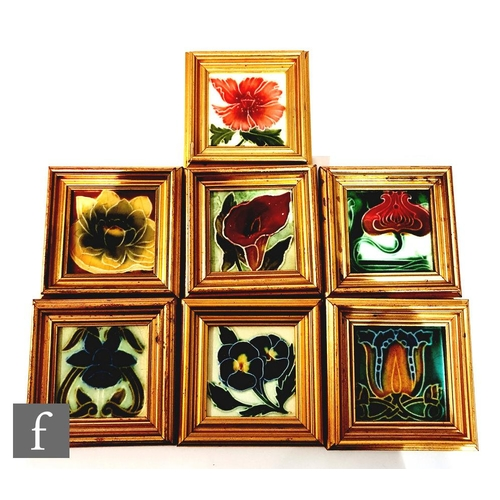 48 - Seven assorted framed 3in Art Nouveau dust pressed tiles, each with a stylised flower head to includ...