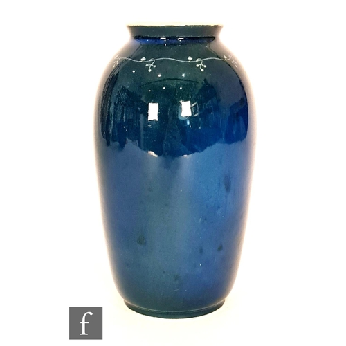 44 - Ruskin Pottery - A souffle glaze vase decorated in a mottled green over dark blue with a hand painte...