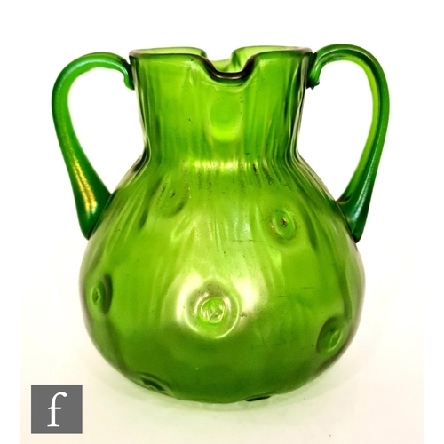 23 - Loetz - An early 20th Century twin handled glass jug of ovoid form with twin lipped collar neck deco...
