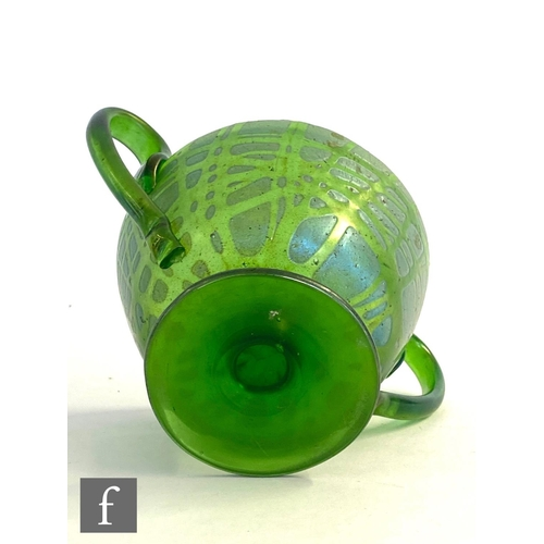 25 - In the manner of Loetz - An early 20th Century glass twin handled pedestal cup in green with a rando...
