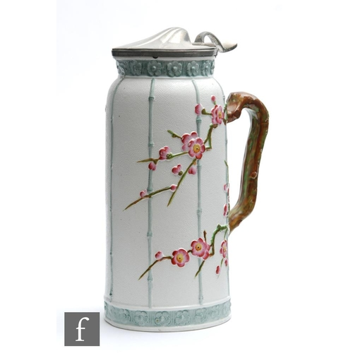 19 - A late 19th Century Aesthetic pewter lidded jug, the body decorated with relief moulded prunus bloss...