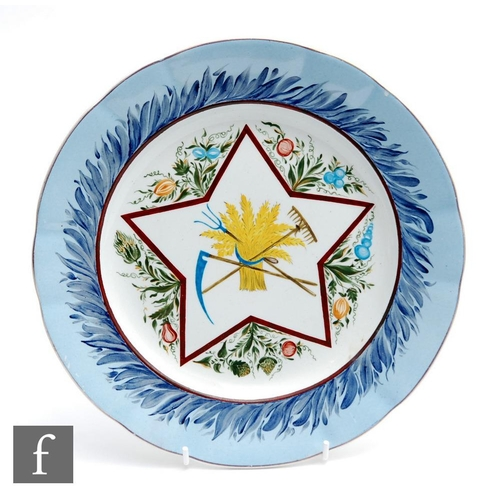40 - An early 20th Century Russian plate, hand painted with a scythe, rake and fork through a bundle of w...