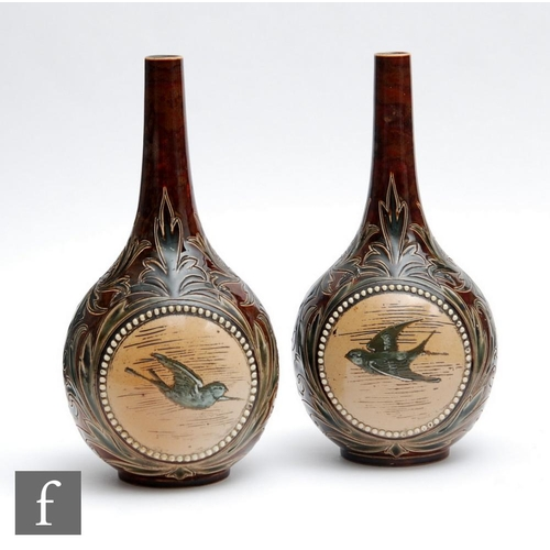 47 - A mirrored pair of late 19th Century Doulton Lambeth bottle vases decorated by Florence Barlow and E...