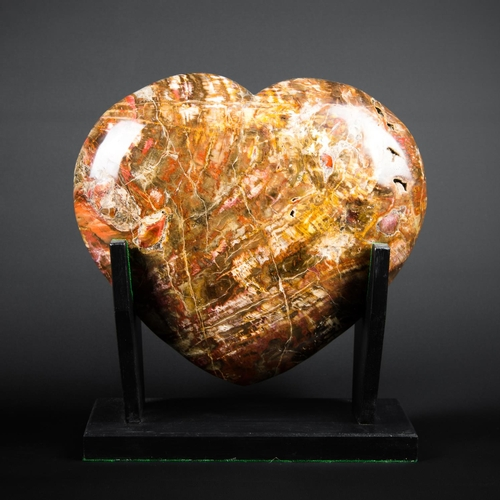 43 - A POLISHED FOSSIL WOOD HEART ON A CUSTOM DISPLAY STAND. (h 30cm x w 25cm x d 12cm)...