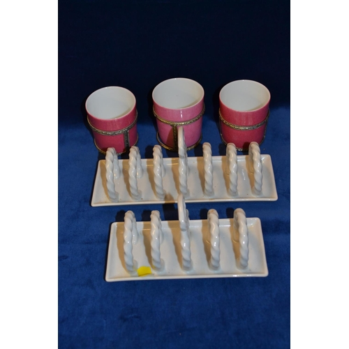 54 - TWO WHITE CHINA ROPE TWIST TOASTRACKS AND 3 PINK LIMOGES COFFEE CANS IN HOLDERS...