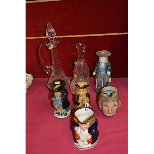 11 - TALL CUT GLASS DECANTER, 2 CARAFS, 4 TOBY JUGS (1 A/F) AND ONE FACE JUG (A/F)...