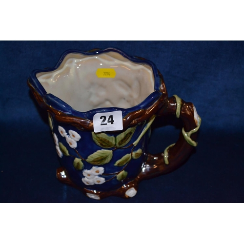 24 - STONEWARE MAJOLICA ALE JUG WITH PRONOUNCED BLOSSOM AND LEAF DECORATION ENTWINED BRANCH HANDLE...