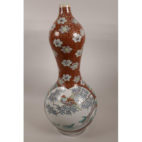 9 - A Chinese gourd shaped vase decorated with panels of exotic birds and flowers on a swirled red groun...