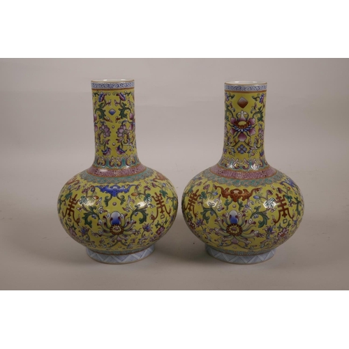 43 - A pair of polychrome porcelain bottle vases with enamelled decoration depicting lotus flowers, bats ...