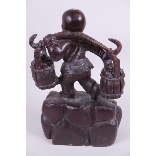 48 - An Oriental carved wood figurine of a boy carrying two baskets on a yoke, 12