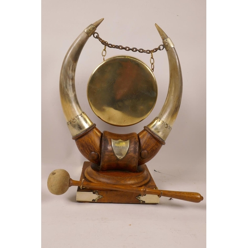 17 - A C19th table top dinner gong, the brass gong supported by a pair of horns mounted on a hardwood sta...