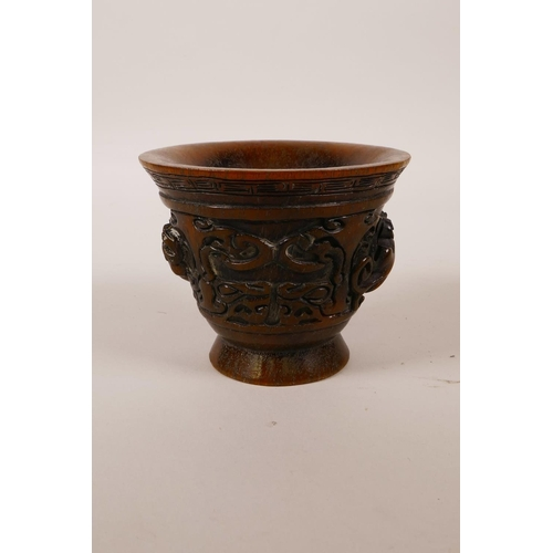 18 - A Chinese faux horn libation cup with two carved handles in the form of kylin, impressed mark to bas...