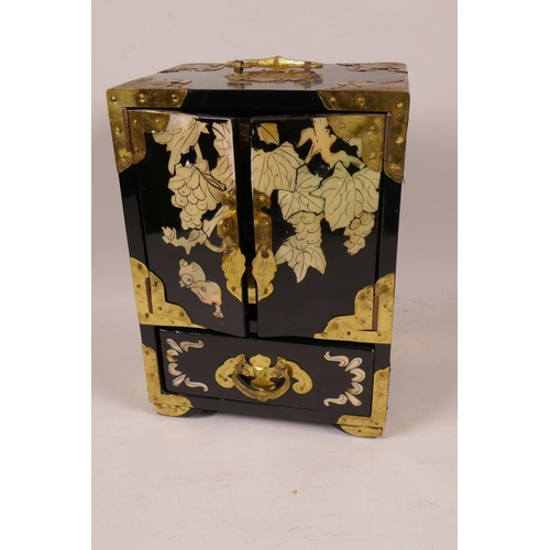 21 - A Chinese brass bound lacquered jewellery box with inlaid decoration, the two doors revealing three ...