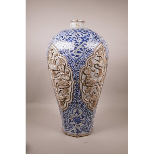 23 - A large Chinese blue and white pottery vase of octagonal form, the panels with raised decoration of ...