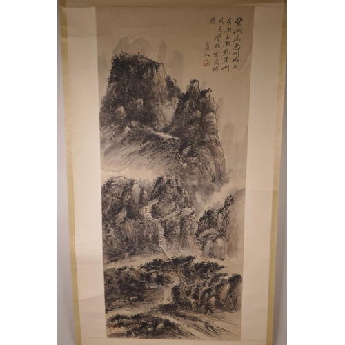 26 - A Chinese watercolour scroll depicting figures on a winding mountain path, 14½