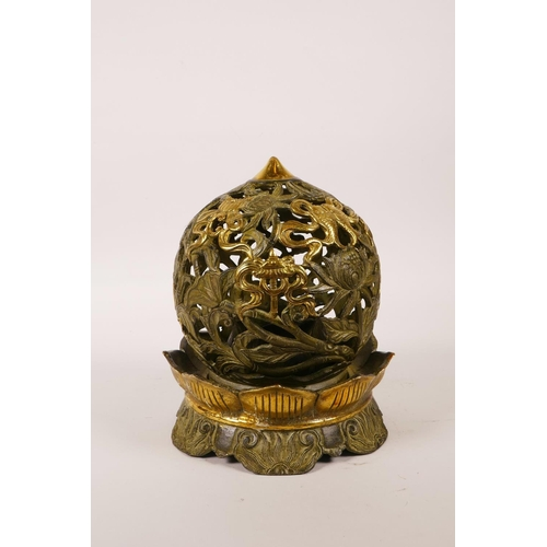 30 - A Chinese pierced bronze ball censer decorated with the eight Buddhist treasures, highlighted with g...