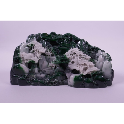 33 - A moulded reconstituted jade ornament depicting a mountainous landscape with temples, 8½