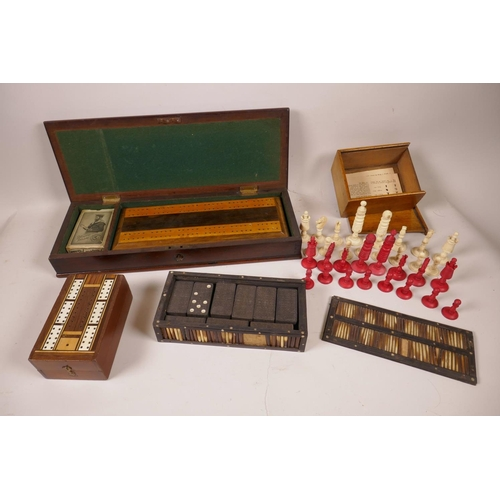37 - A mahogany box containing an inlaid cribbage board with bone markers and a vintage set of playing ca...