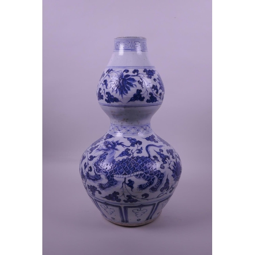 38 - A Chinese blue and white pottery double gourd vase decorated with lotus flowers and kylin, 13½